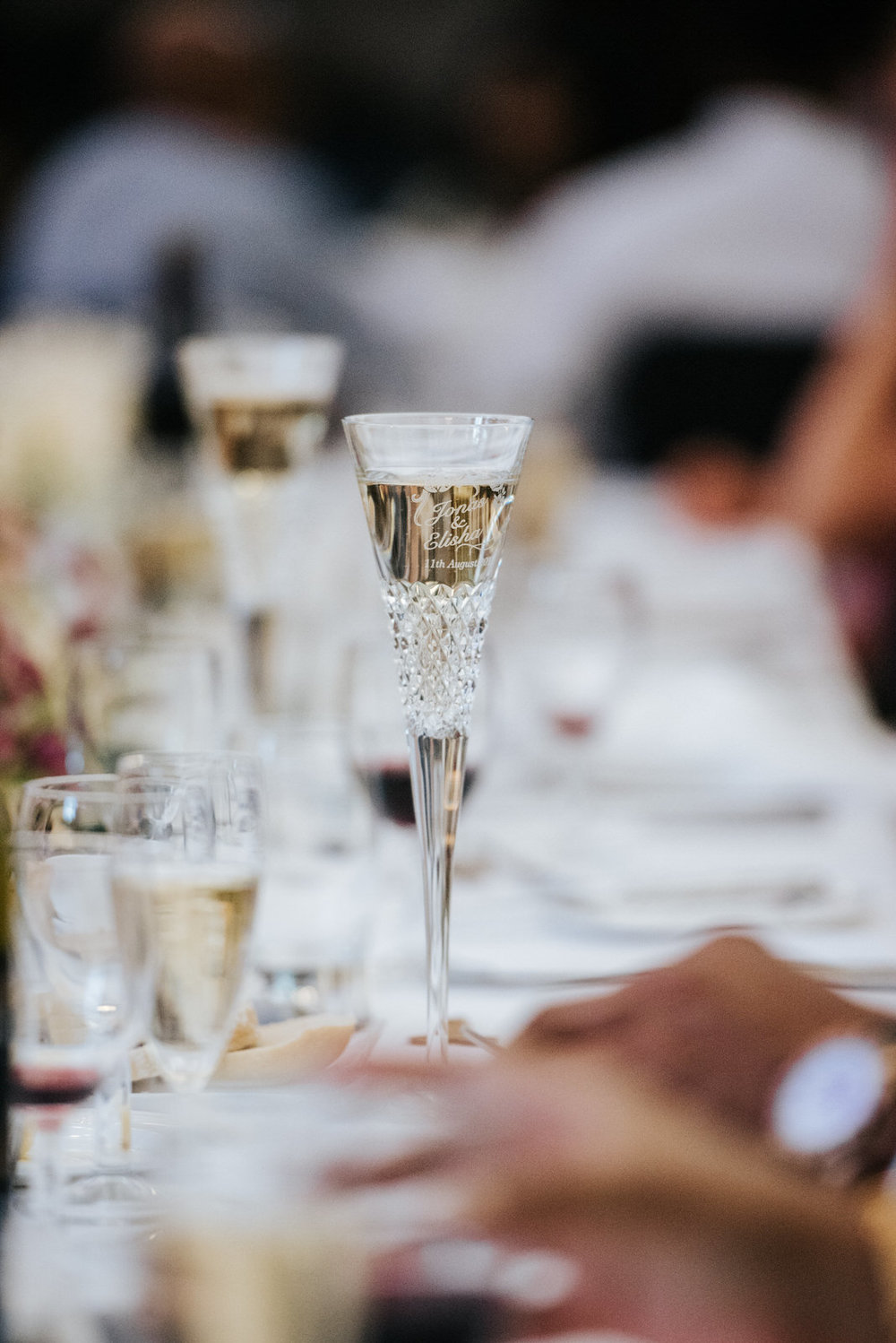Detail photograph of champagne glasses which have the bride and
