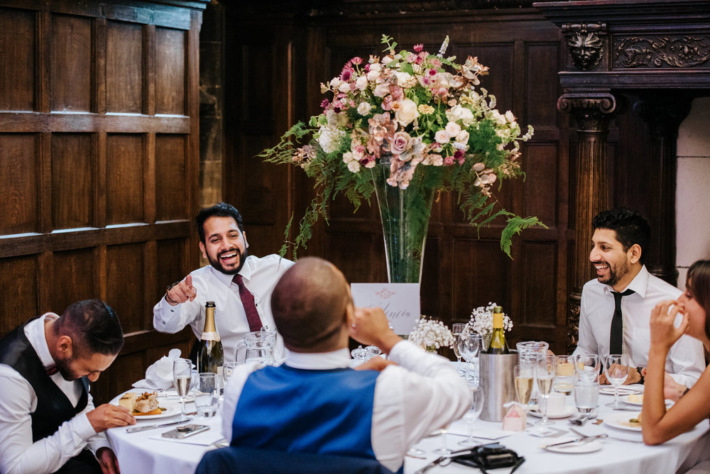 Guests laugh at one of the tables as they eat dinner