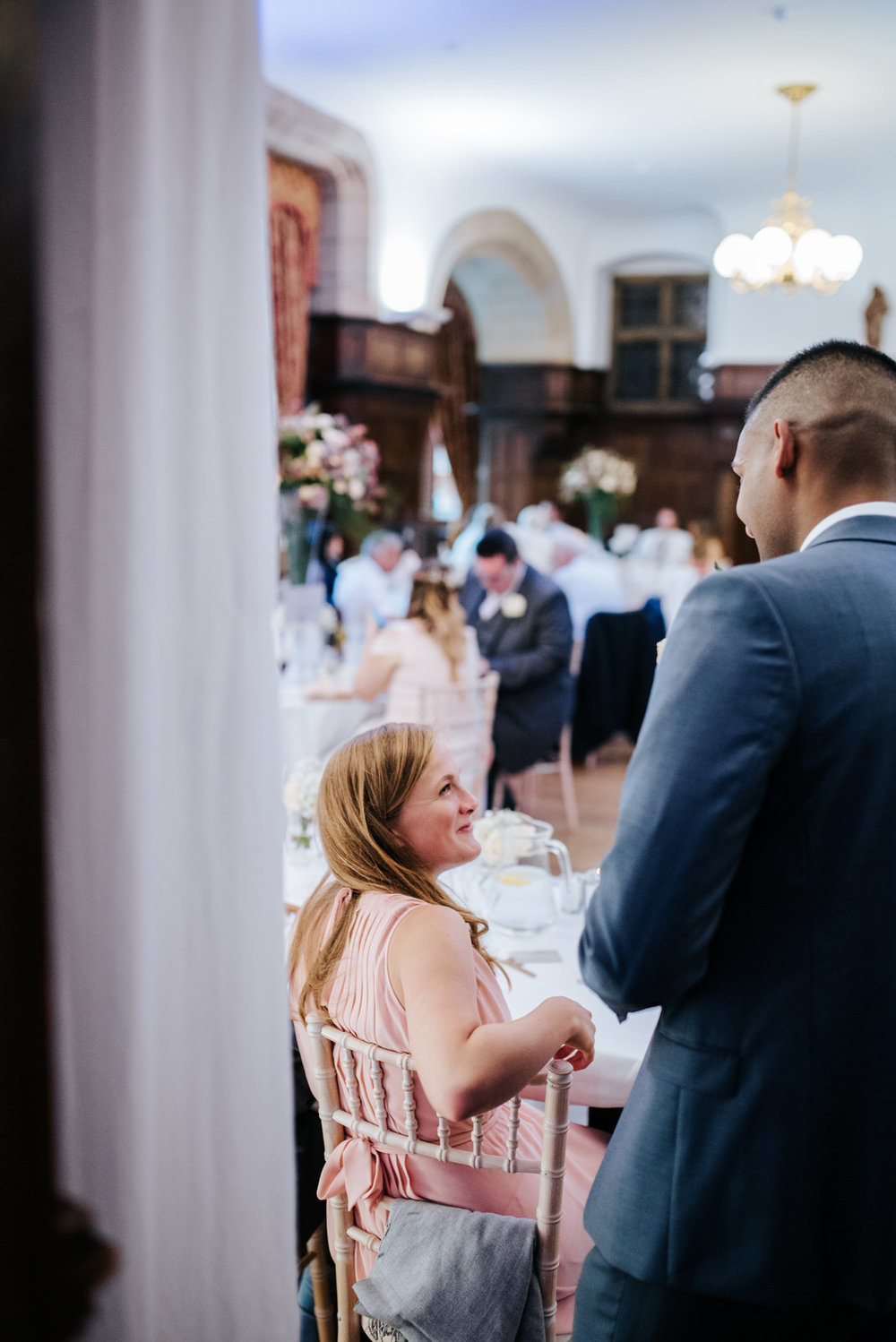 Groom talks to guest while she sits and smiles
