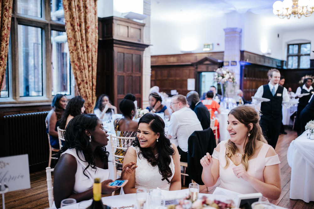 Bride sits and smiles with two guests while food is being served