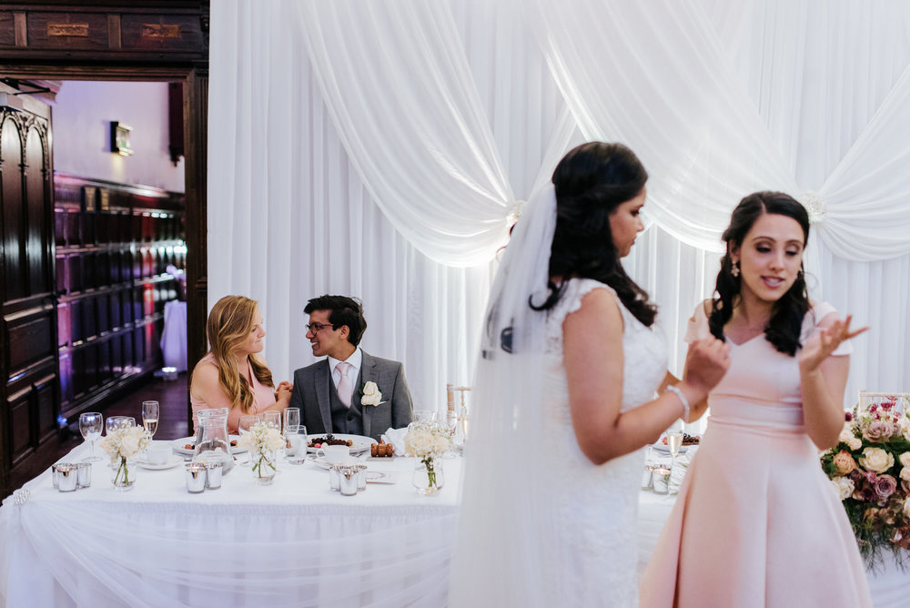Bride's brother and his girlfriend sit and smile at each other d