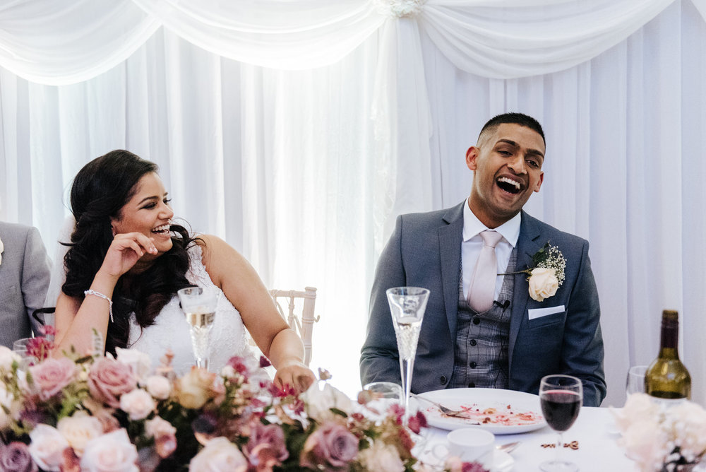 Groom cannot contain his laughter as speeches as delivered durin