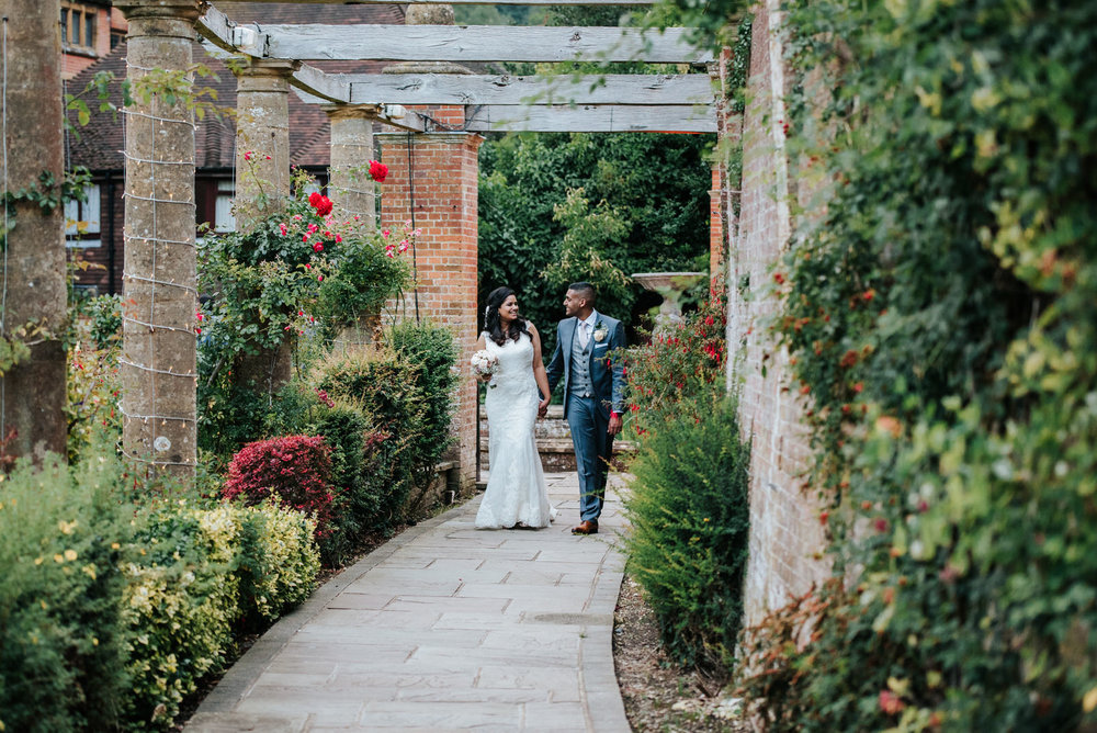 Bride and groom walk through beautiful garden at Woldingham Scho