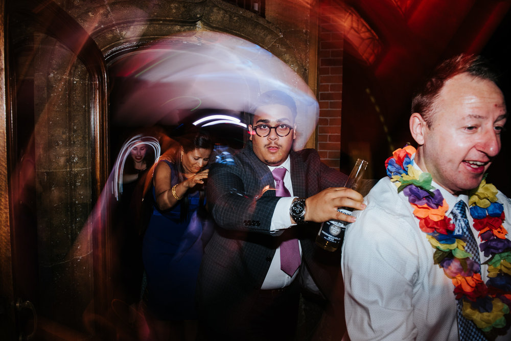 Guests form a train under disco lights at Woldingham School wedd