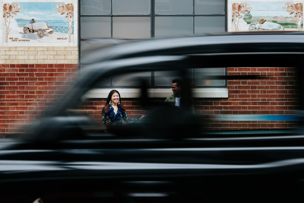 Bride looks at camera while blurred taxi drives by in London eng