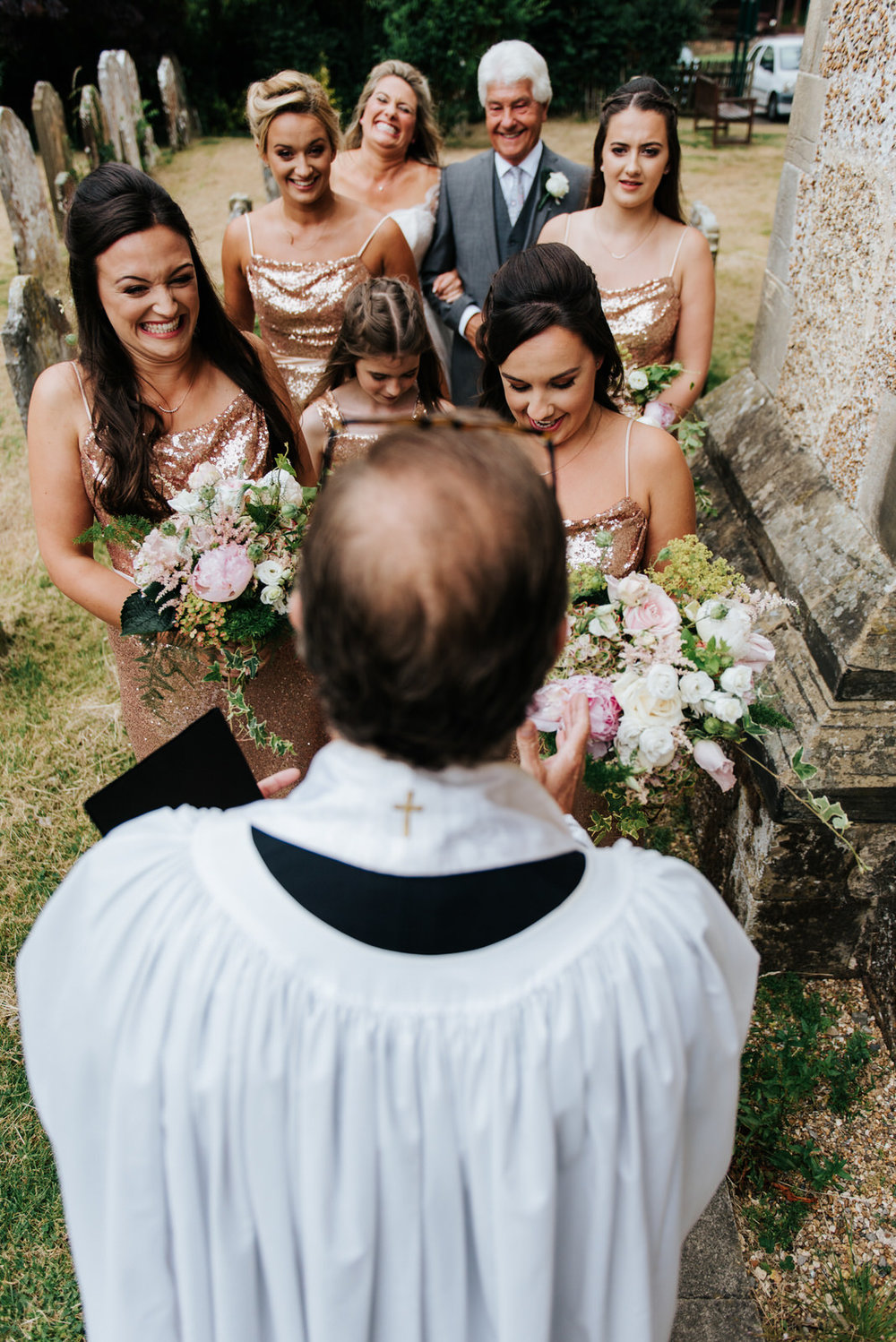 Vicar speaks to bride and bridesmaids before they go into church