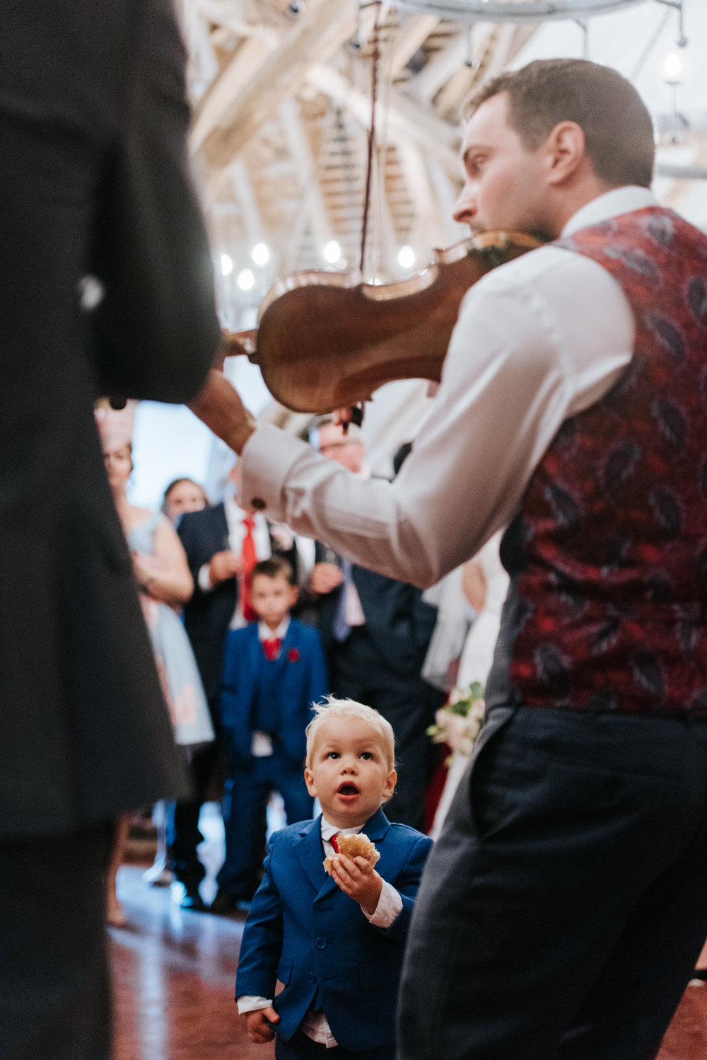 Kid looks up at groom playing violin at Colville Hall Essex
