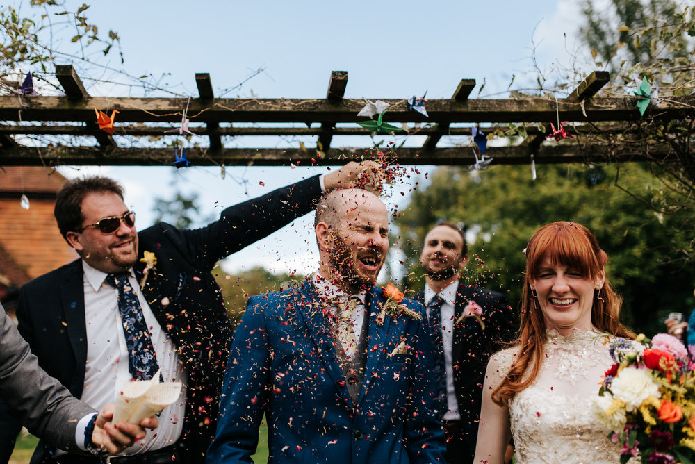 Groom and bride have confetti thrown at them after wedding cerem