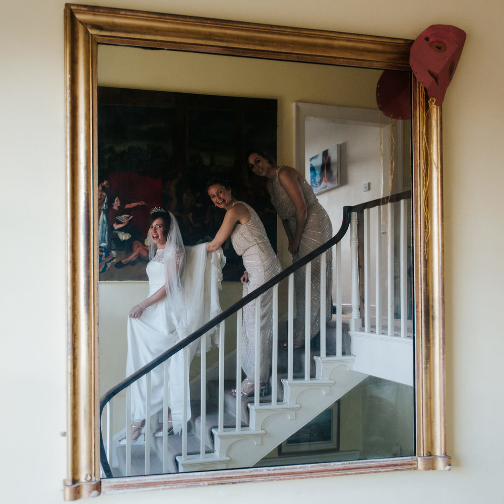 Bride and bridesmaids look into the mirror and see themselves du