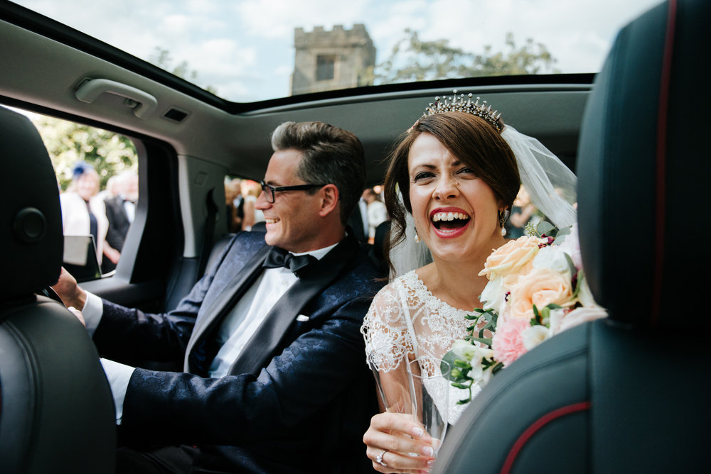 Bride and groom inside car opening a bottle of champagne and smi