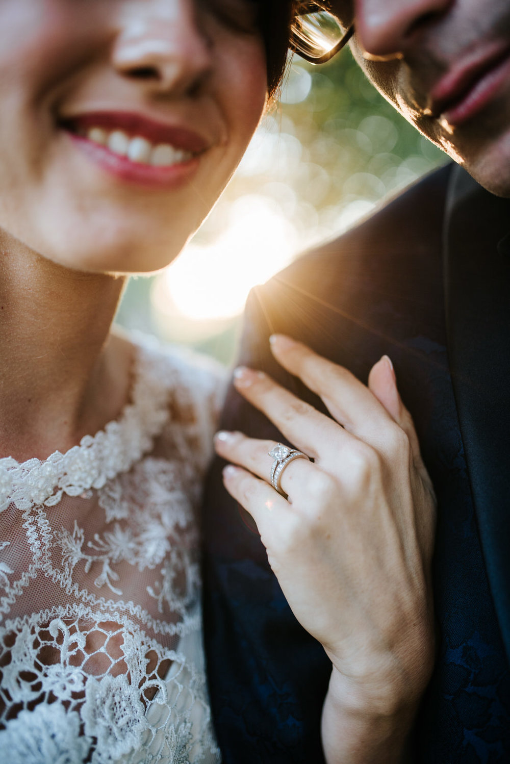 Bride shows off diamond ring as sun sets behind them during wedd