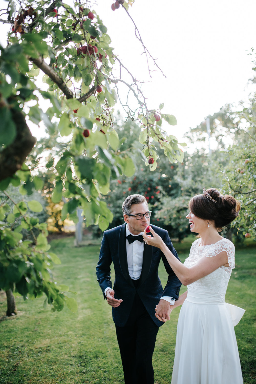 Bride and groom laugh and eat a plum during evening wedding phot