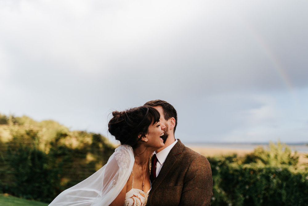 Bride smiles as groom kisses her and rainbow forms behind them i