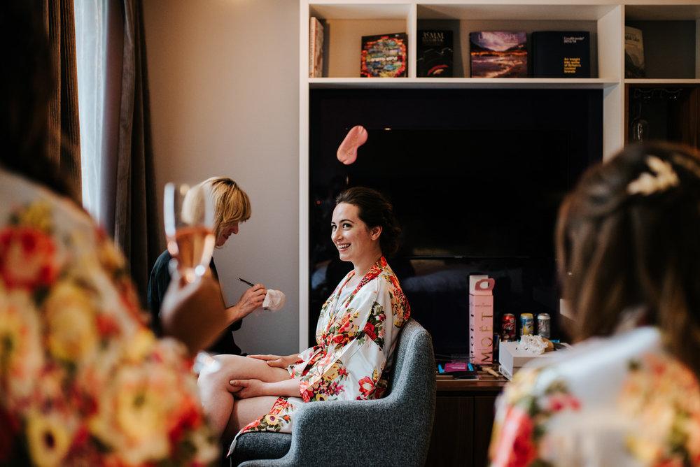 Bride looks happily towards bridesmaids sat across her