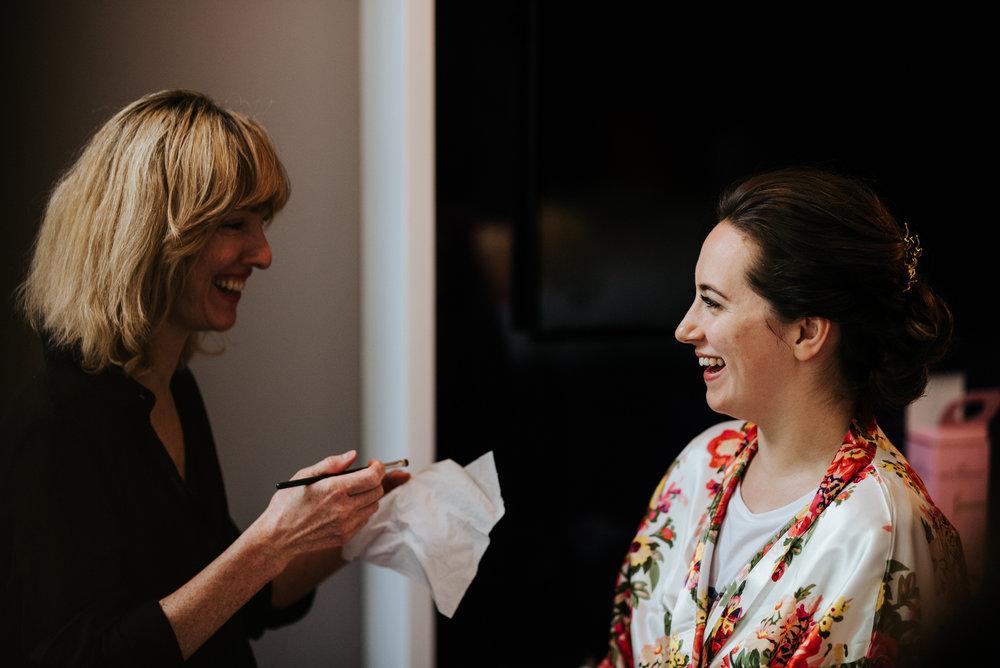 Bride smiles in robes as make-up artist begins working