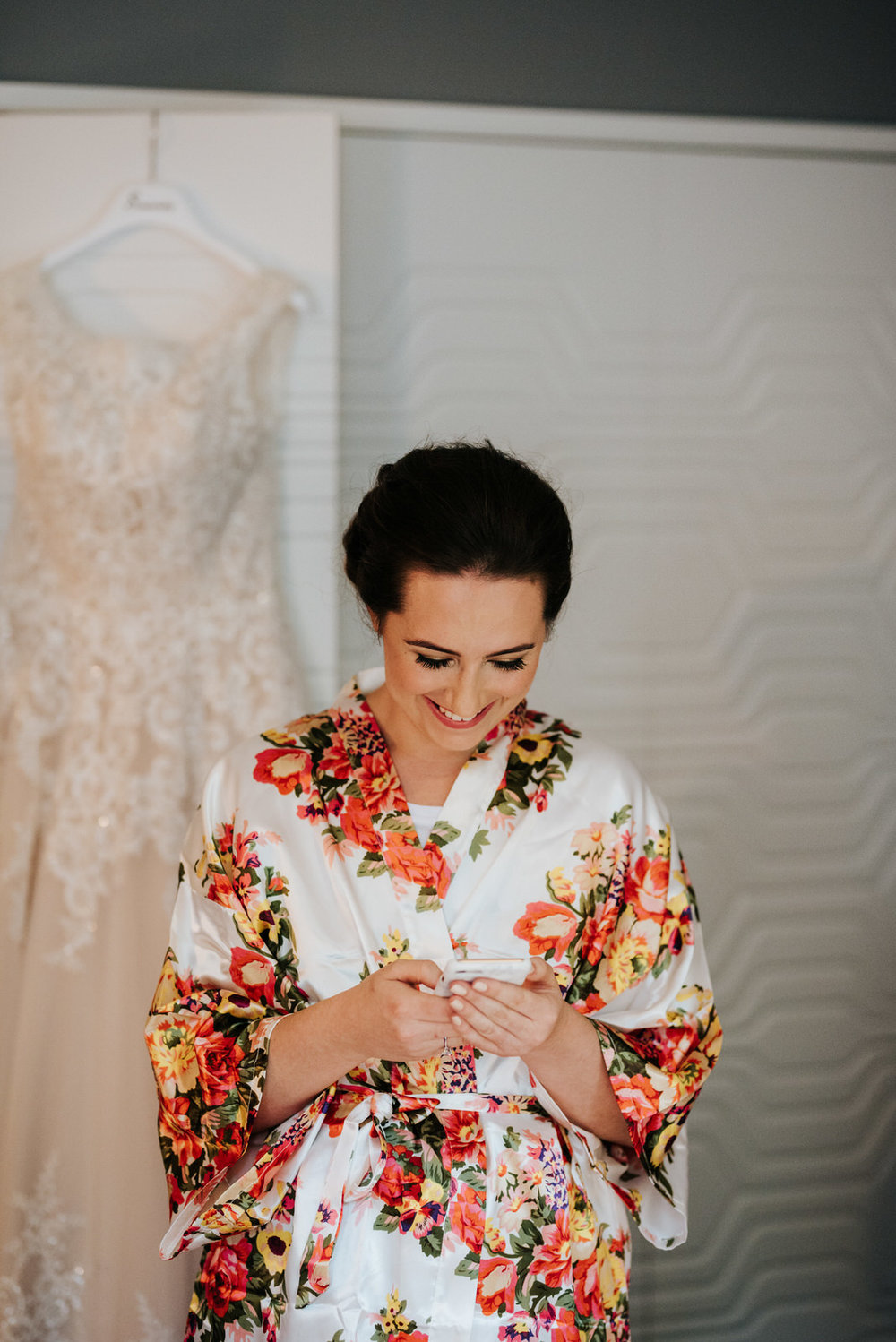 Bride looks and smiles at phone as she reads a text message