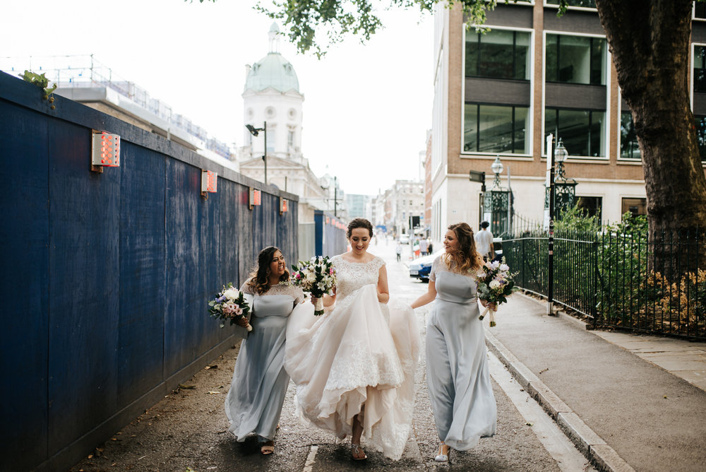 Bride and bridesmaids walk on the streets of London as they hold