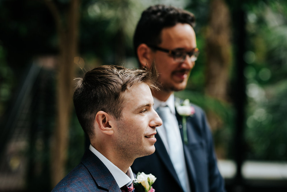 Groom and his best man wait at the front of the aisle