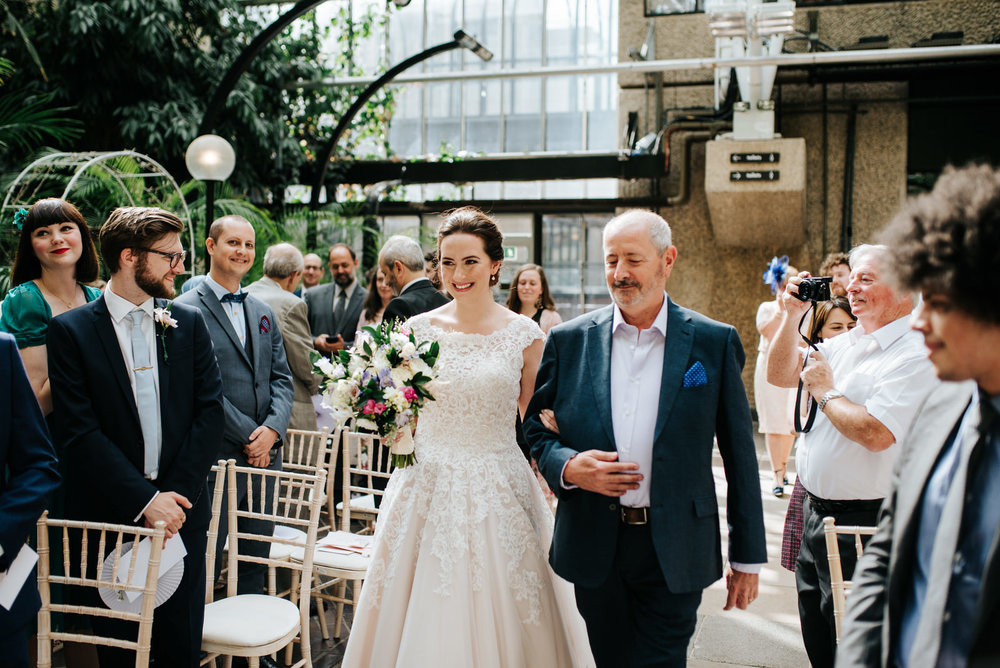 Bride and her uncle approach the end of the aisle as bride meets