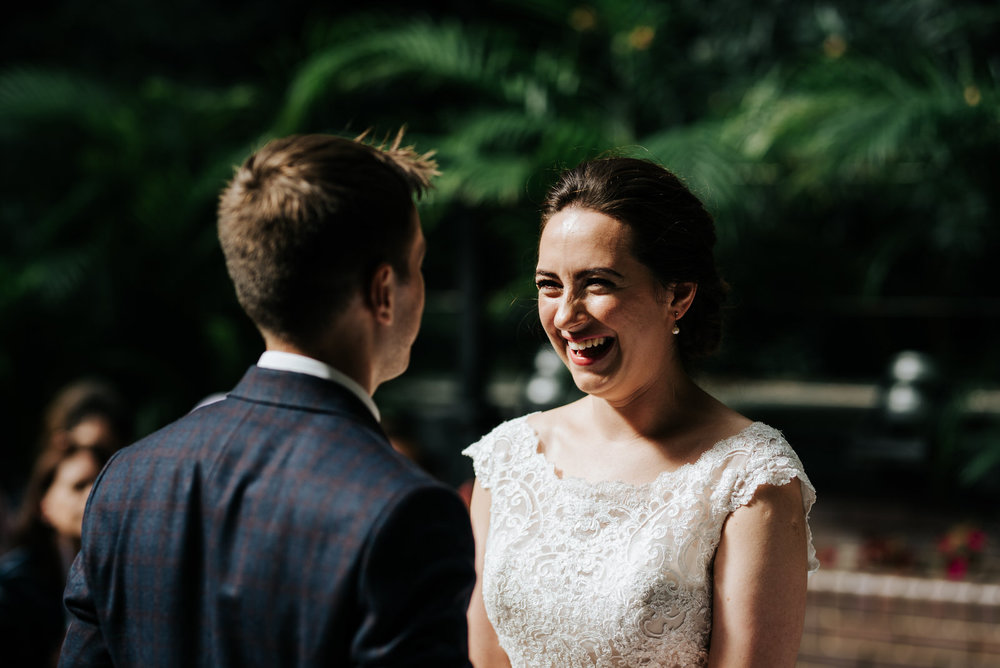 Bride and groom hold hands and exchange vows as bride has an out