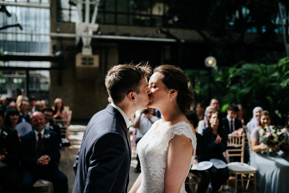 Bride and groom share their first kiss in beautiful, dappled lig
