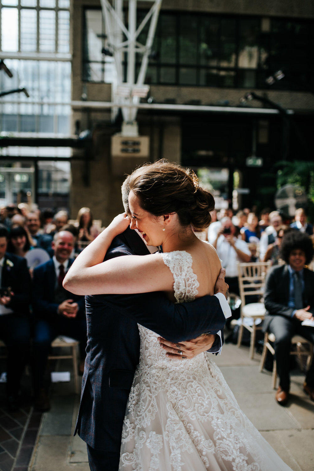 Bride and groom embrace each other in a joyful hug after sharing