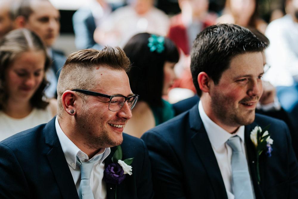 Two groomsmen smile and look joyfully towards bride and groom