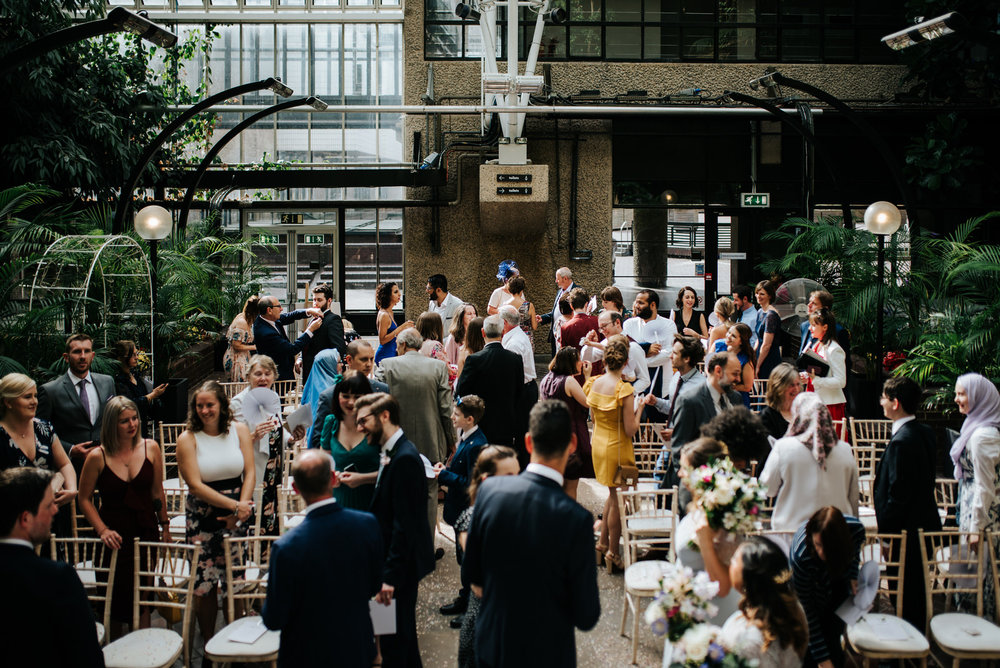Wide photograph of guests mingling inside barbican wedding venue