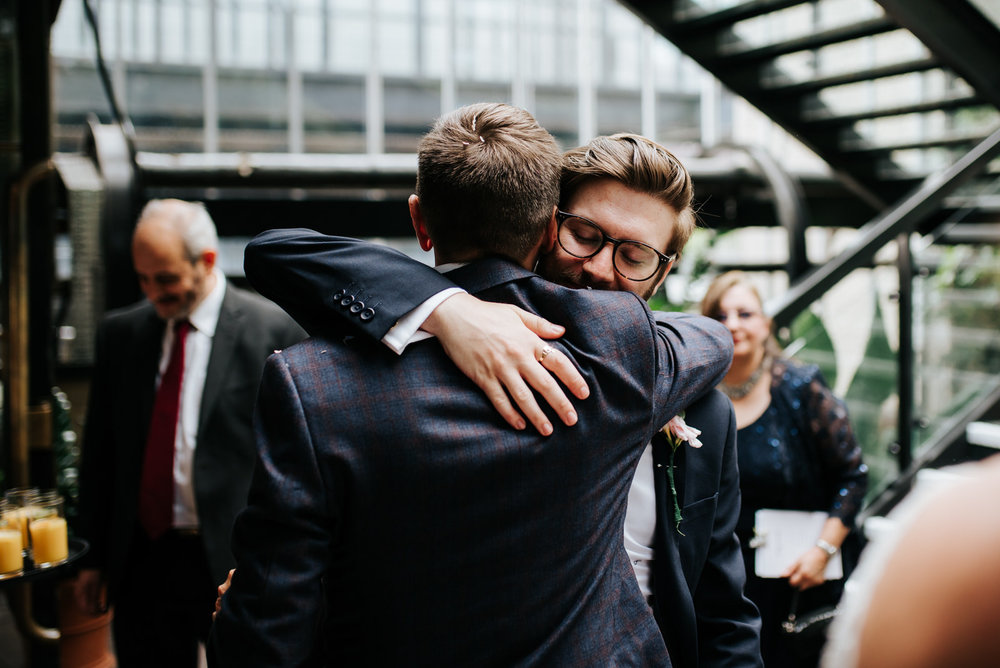 Groom and groomsman hug and embrace each other after wedding cer