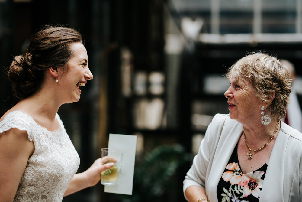 Bride smiles at family member as everyone says hello after weddi
