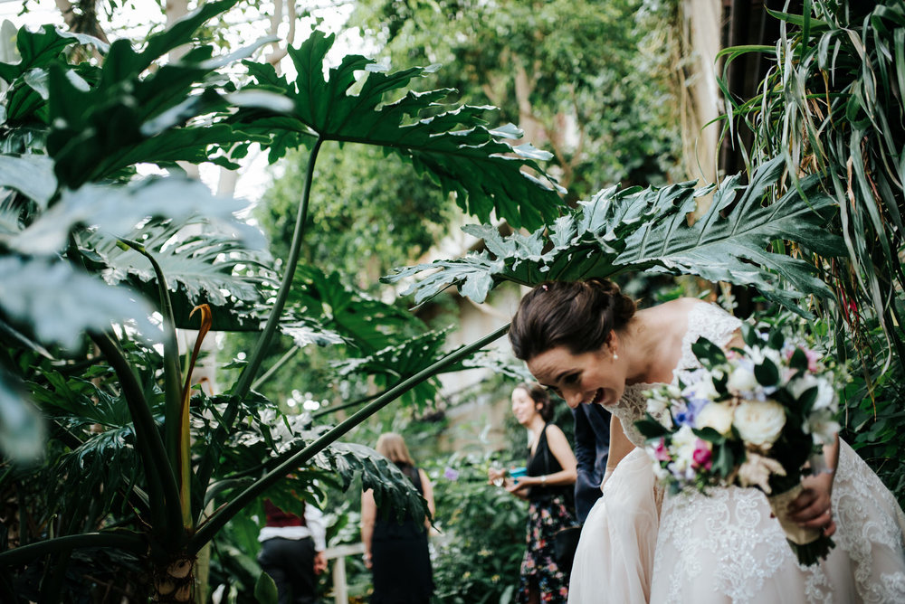 Bride laughs as she dodges massive green leaf on her way to wedd