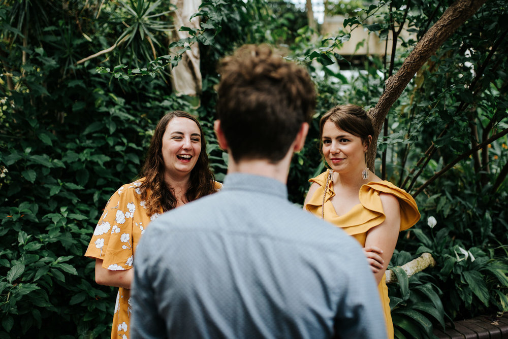Three guests look at each other and smile during wedding canapes