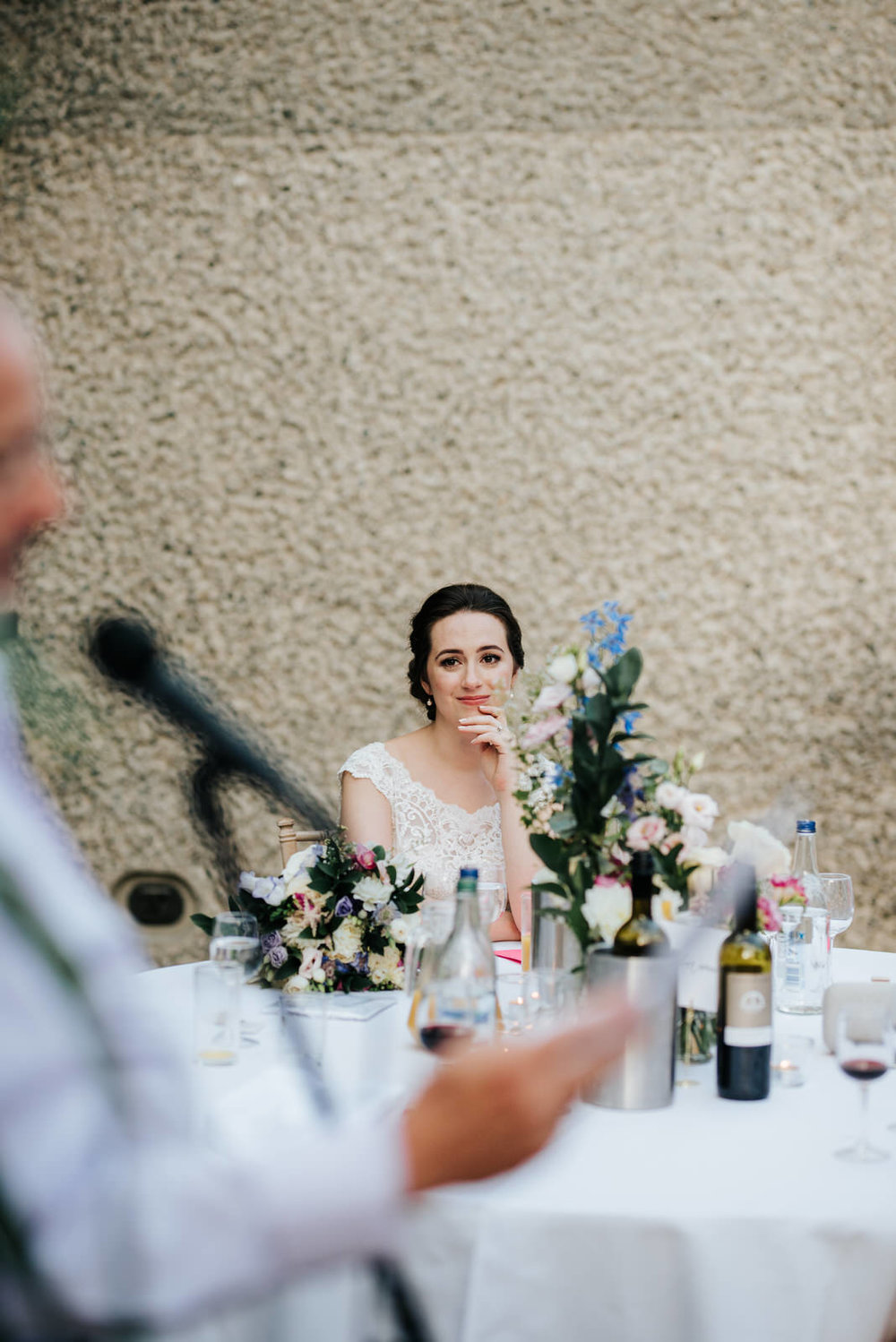 Bride looks emotional and grateful as close family member delivers a wedding speech