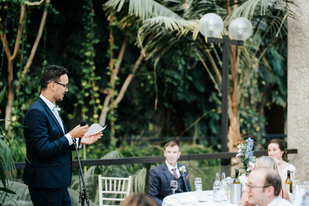 Best man delivers heartfelt speech while bride and groom listen