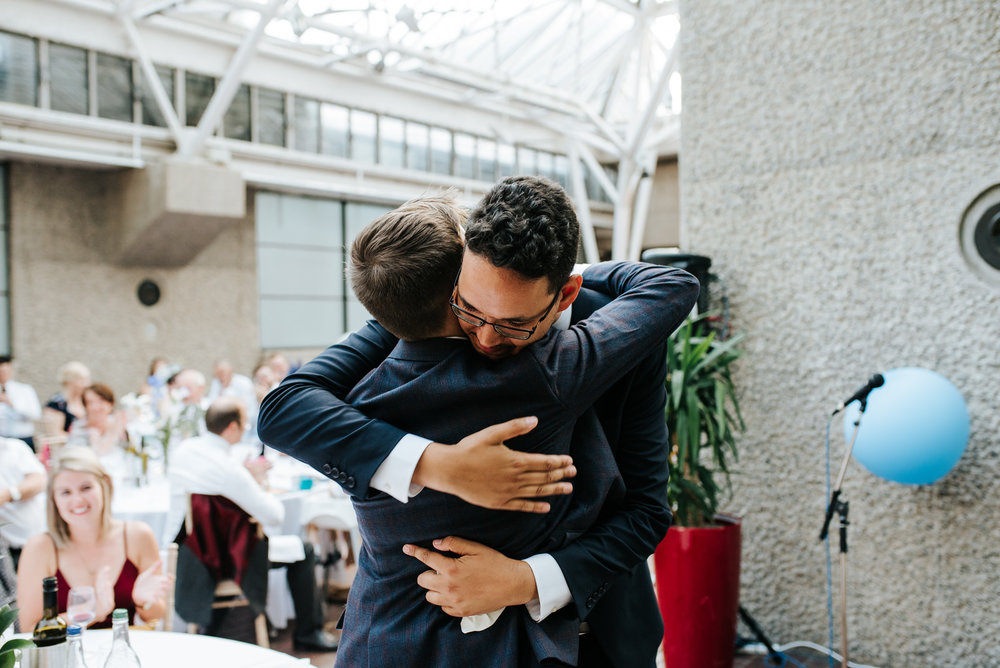 Best man hugs groom as guests smile from the back
