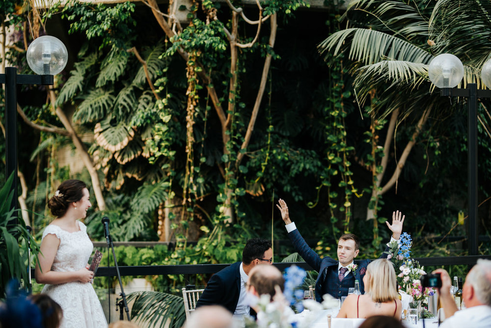 Groom raises both hands towards the air in celebratory gesture a