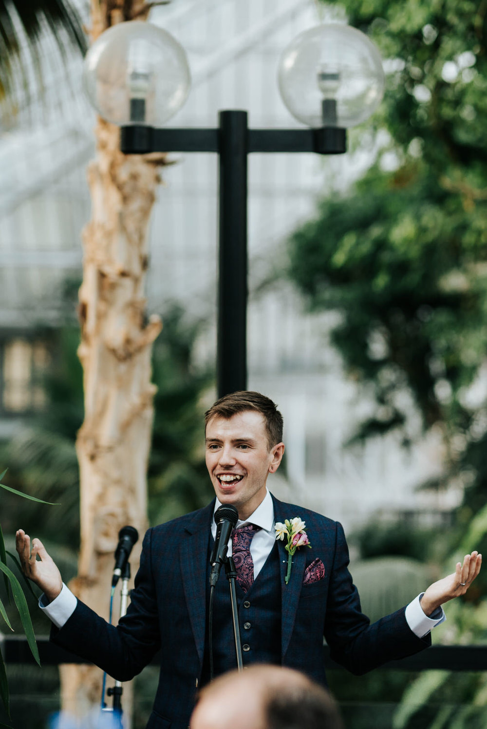 Groom looks happy and amused as he starts delivering his wedding