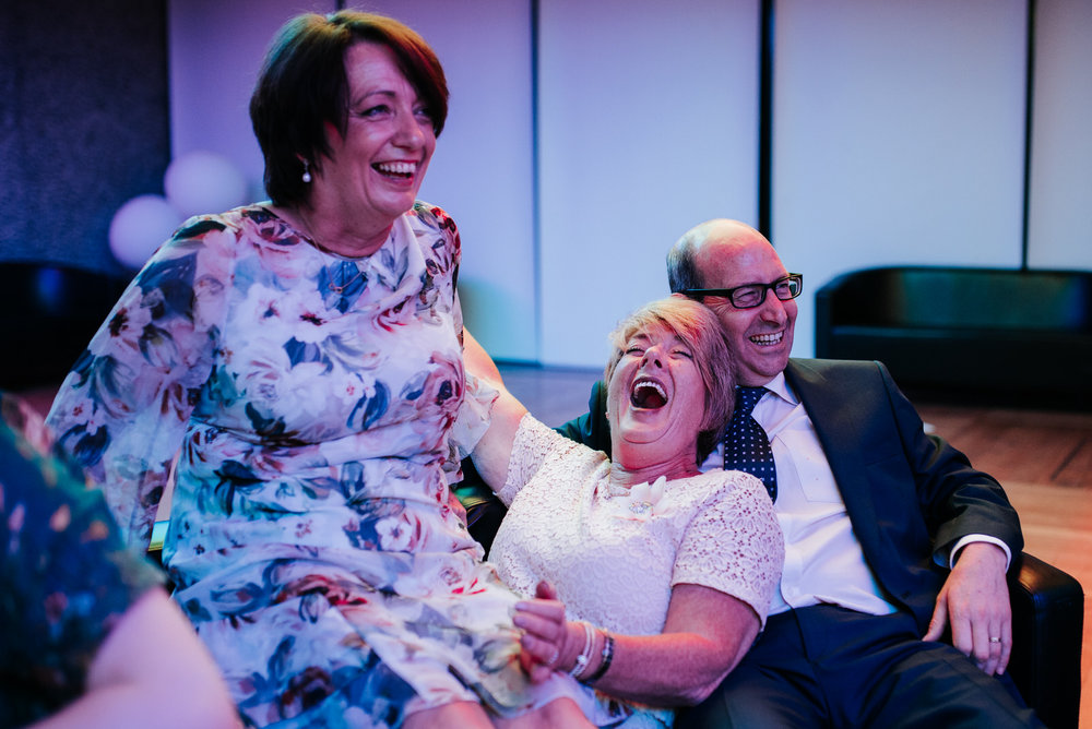 Bride's aunties sit on top of each other and laugh while one of