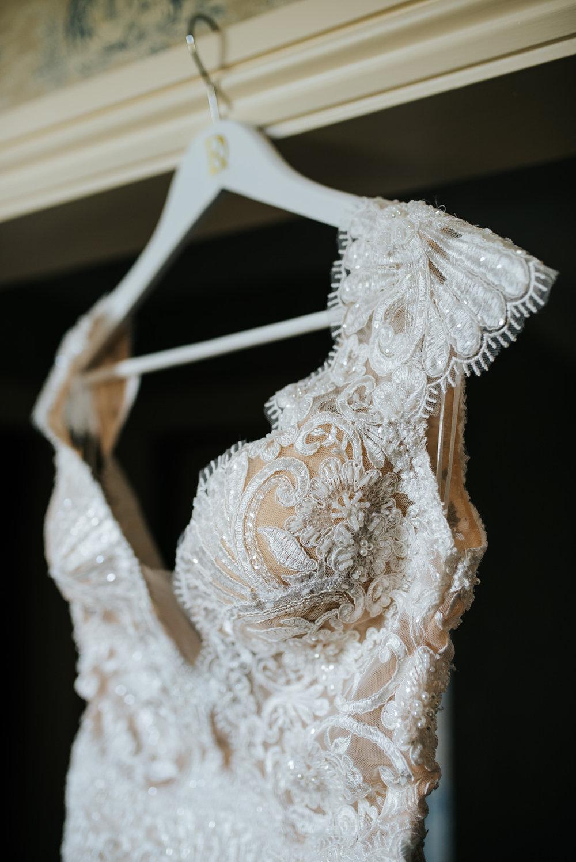 Bride's beautiful lace-detailed dress hangs on door