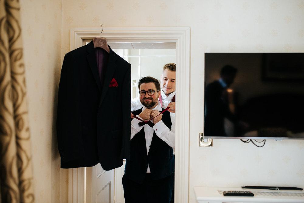 Groom stands by door as groomsman helps him put on his tie