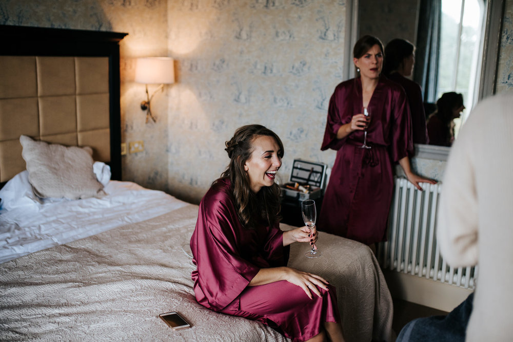 Bride's sister sits on bed and smiles while holding glass of prosecco