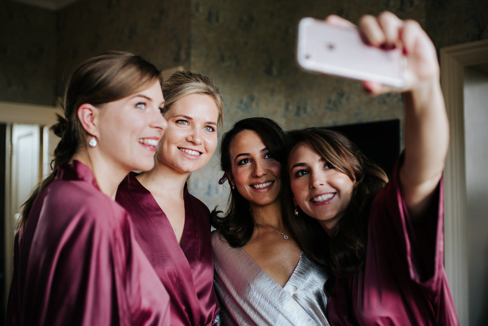 Bride and bridesmaids take a selfie in wedding robes