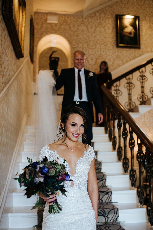 Bride walks down hotel stairs at The Petersham as step-dad holds her veil behind her