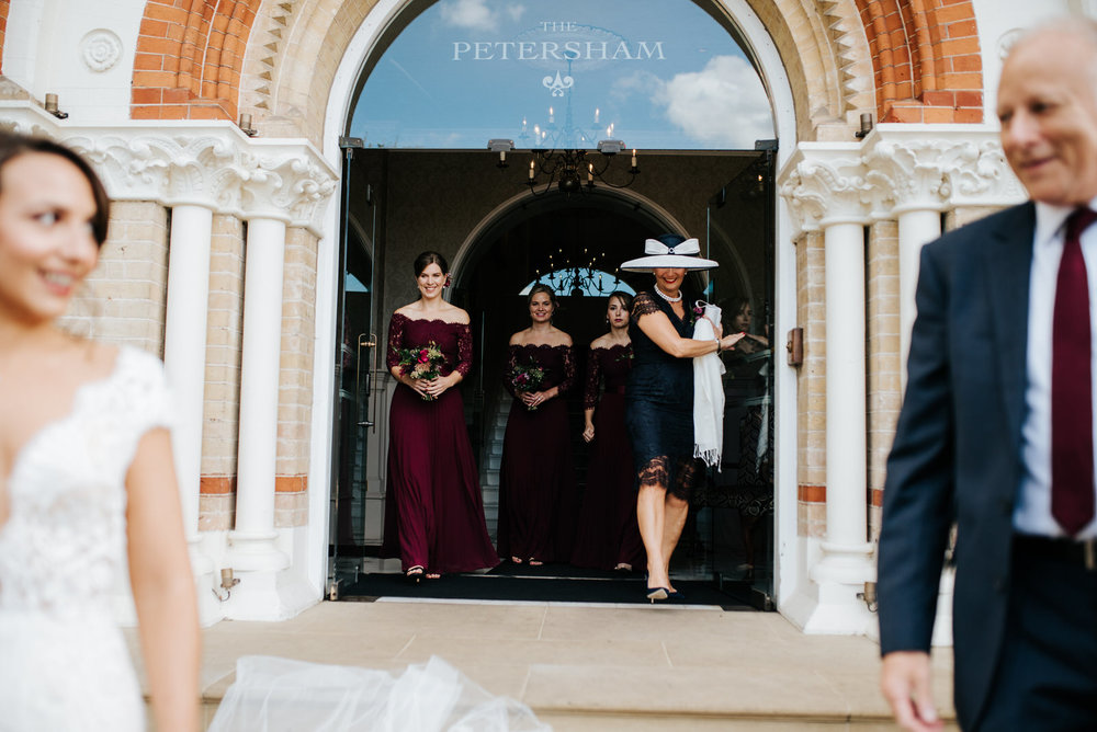 Bride and step-dad walk out of The Petersham as mum and bridesmaids smile from behind