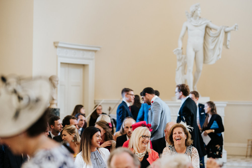 Guests smile and laugh as they wait for wedding ceremony to begin in Syon House
