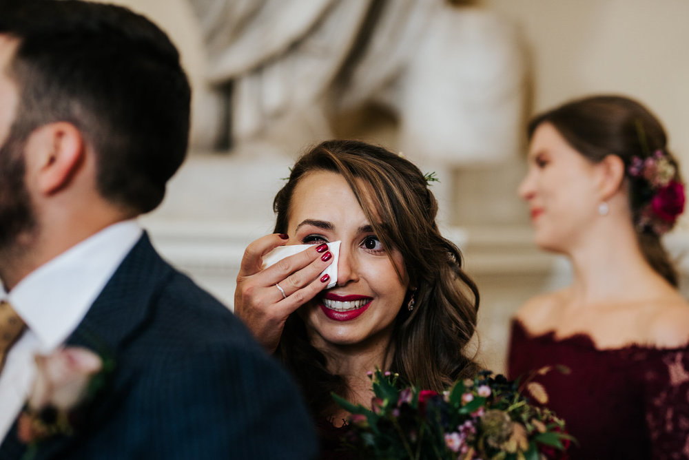 Bride's sister smiles and cries as bride walks down the aisle