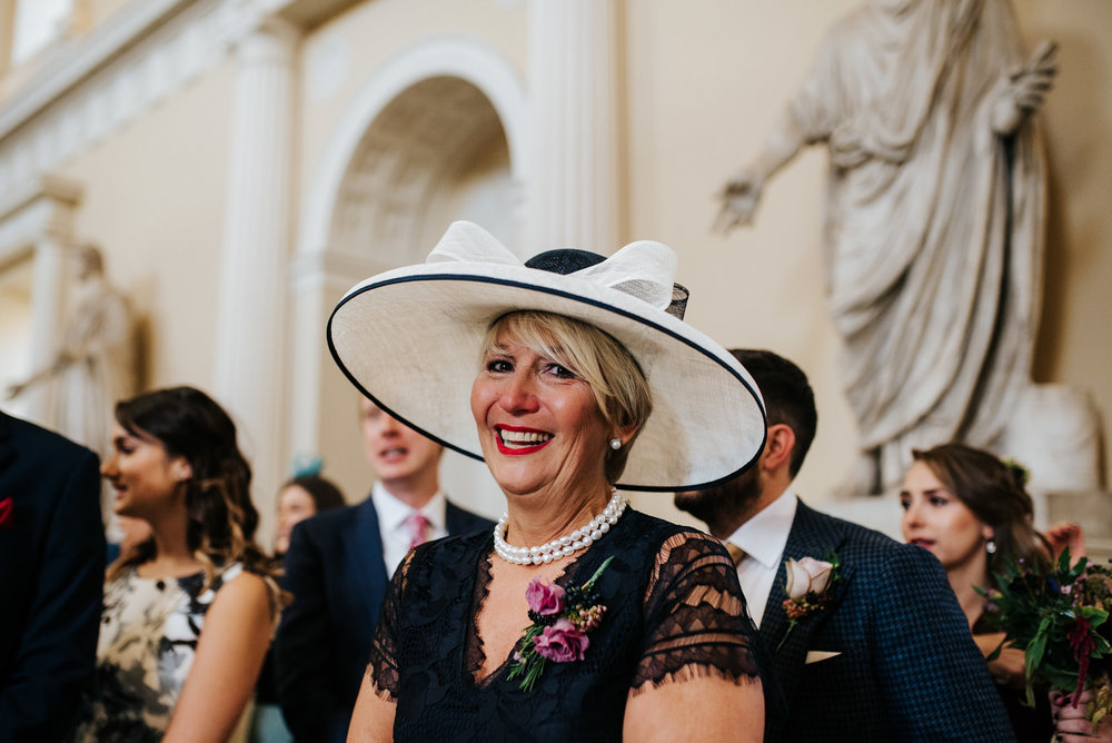 Bride's mum wears stunning  hat and smiles at camera as bride comes down aisle
