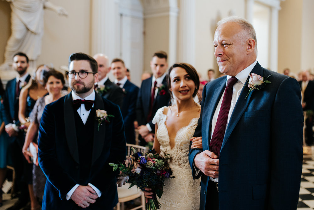 Bride smiles at step-dad as he holds her close and looks proud
