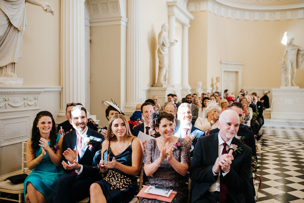 Groom's side of the family laughs and applauds as ceremony comes to an end