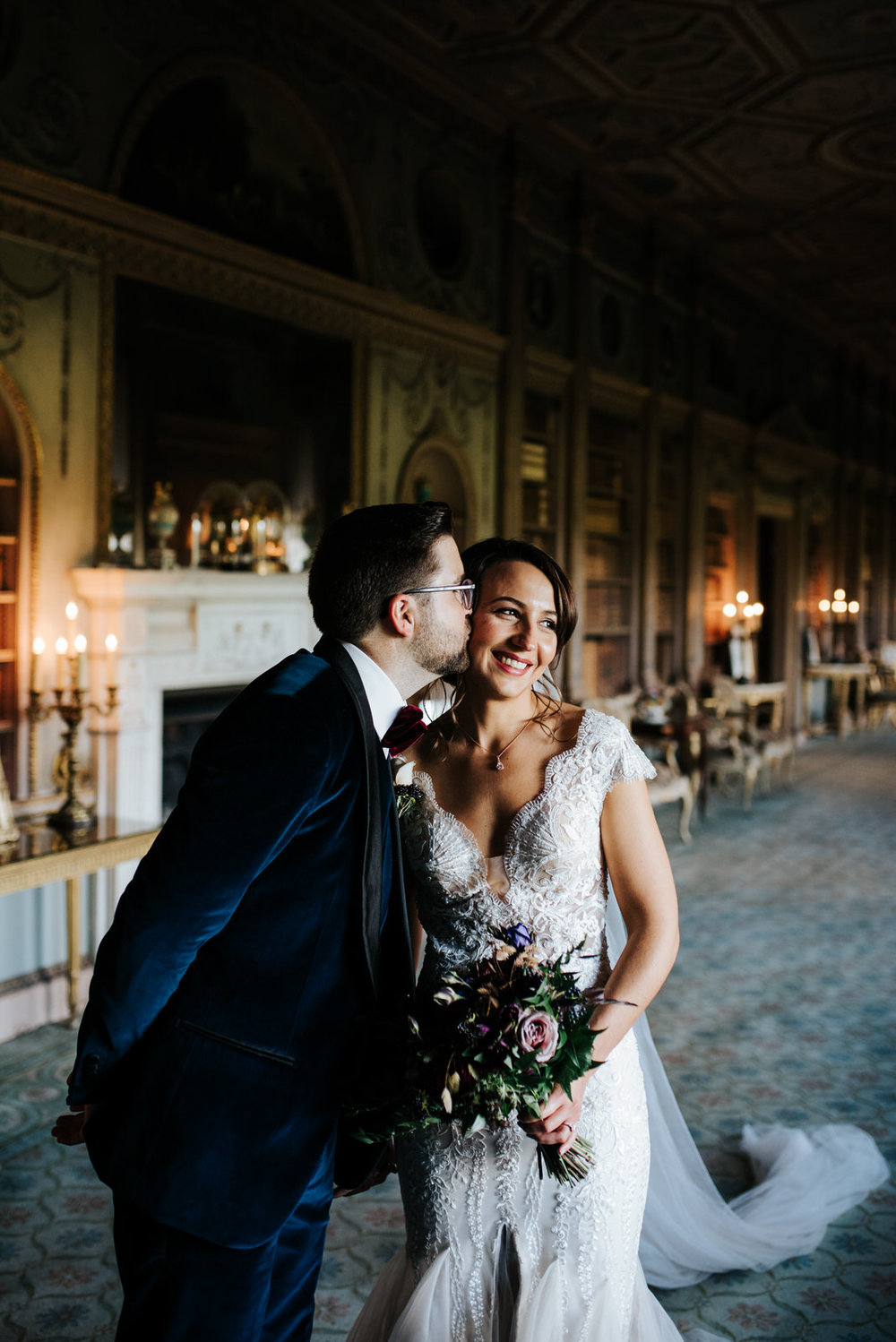 Bride and groom smile as they have their photo taken in Syon House's Library room